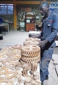 Mitarbeiter*innen von Mayondo Woodworks Ltd., Uganda bei der Produktion der Zahnräder für den Kalender. Foto:©MansuliMayondo