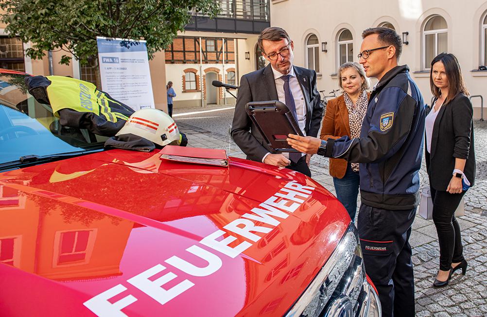 Innenminister Roland Wöller lässt sich die App erklären