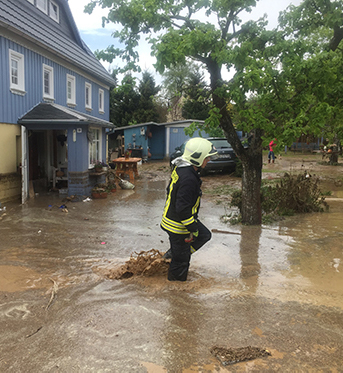 Ein Feuerwehrmann läuft durch Schlamm und Wasser.